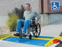 man in wheel chair easily crossinng linebacker cable protector with blue ada ramp kit attached